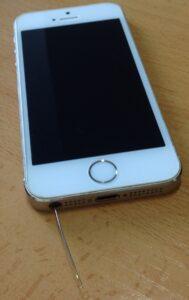 iPhone con una aguja de coser dentro del puerto de los auriculares.