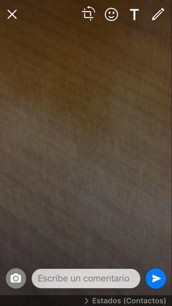 Cámara de un iPhone tomando una foto para un estado de WhatsApp, en donde se puede observar un icono en forma de avión de papel.